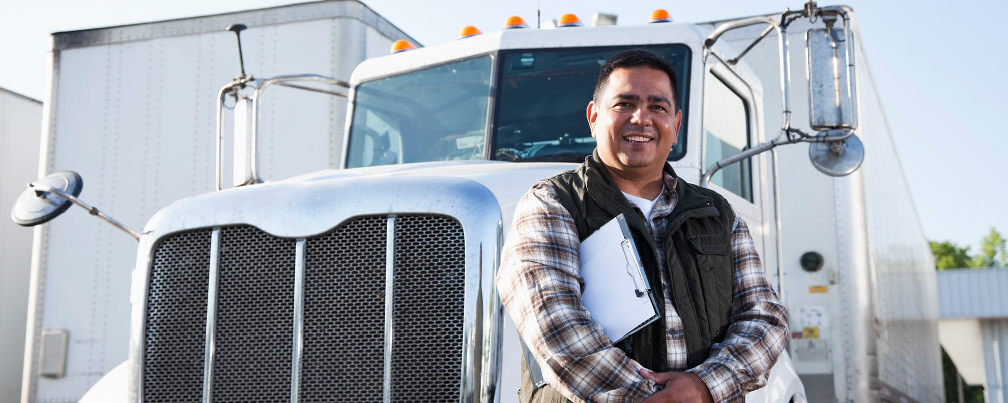 Image of smiling man standing in front of his tractor-trailer